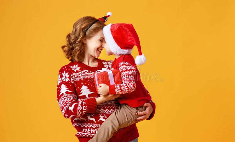Happy family mother and child son with christmas gifts on yellow background stock images