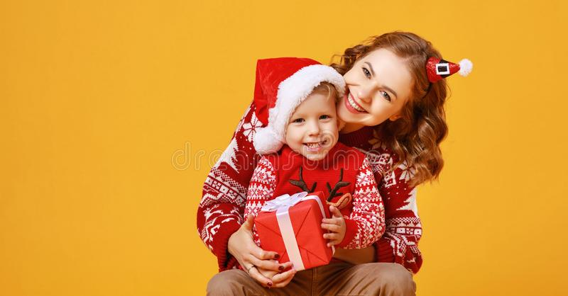 Happy family mother and child son with christmas gifts on yellow background royalty free stock photography