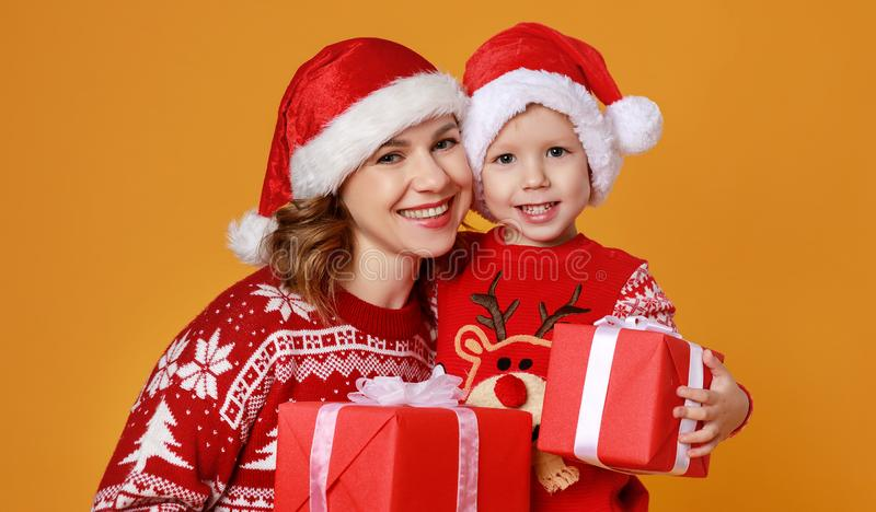Happy family mother and child son with christmas gifts on yellow background royalty free stock photos