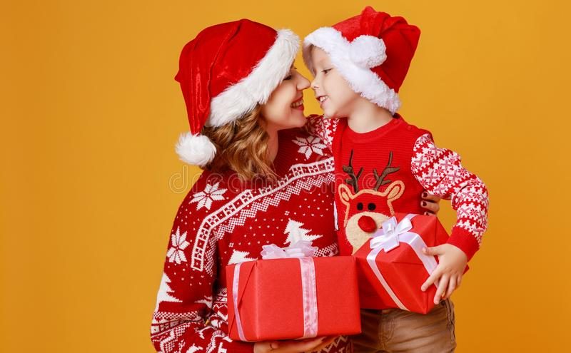 Happy family mother and child son with christmas gifts on yellow background royalty free stock image