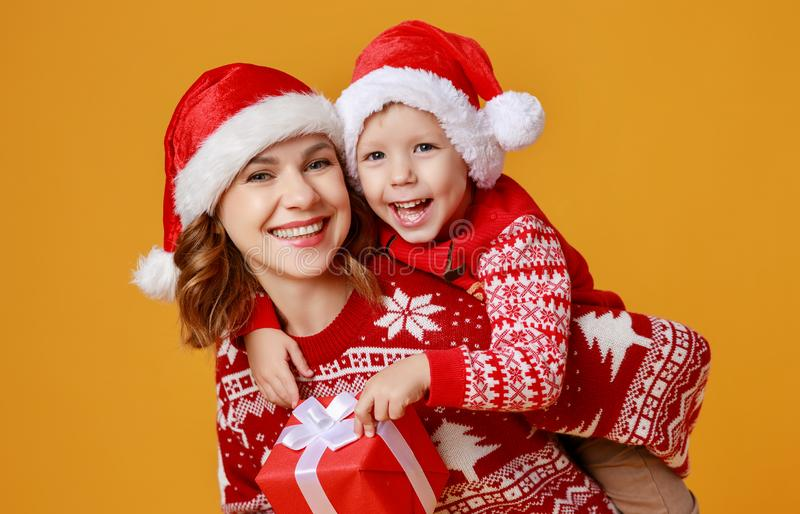 Happy family mother and child son with christmas gifts on yellow background royalty free stock photo
