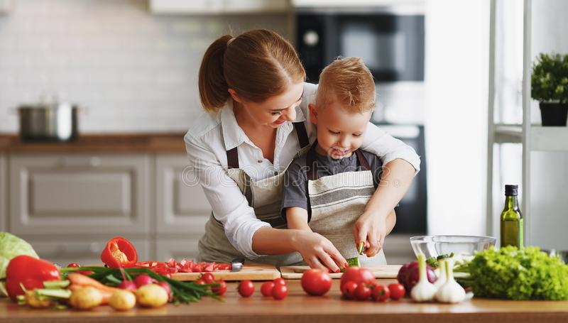 Happy family mother with child son preparing vegetable salad royalty free stock images