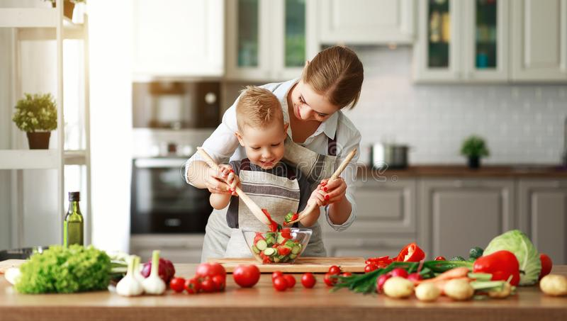 Happy family mother with child son preparing vegetable salad royalty free stock image