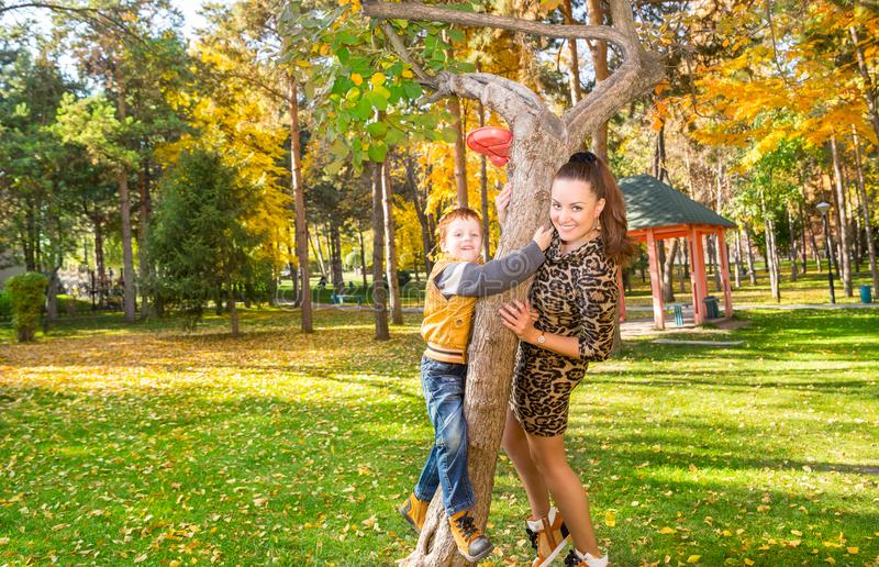 Happy family: mother and child sonr have fun in autumn on autumn park. Young Mother and kid girl hugging in leaves at fall. royalty free stock photography
