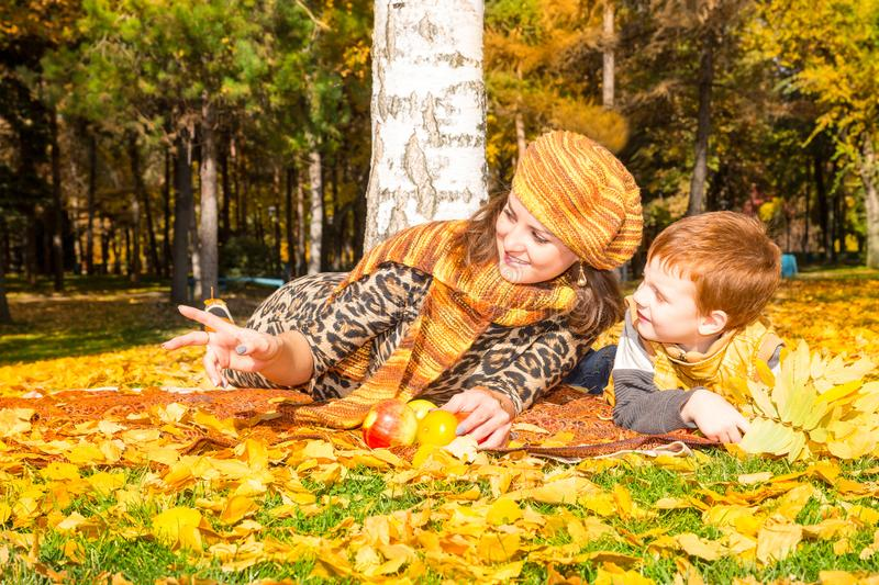 Happy family: mother and child sonr have fun in autumn on autumn park. Young Mother and kid girl hugging in leaves at fall. stock photography