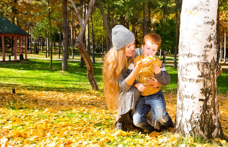 Happy family: mother and child sonr have fun in autumn on autumn park. Young Mother and kid girl hugging in leaves at fall. royalty free stock images