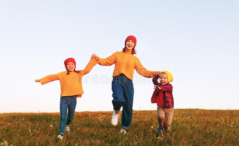 Happy family mother and children in autumn nature at sunset. Happy family mother and children running in autumn nature at sunset royalty free stock images