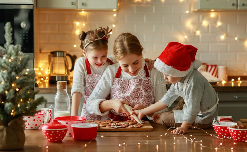 Happy family mother and children bake christmas cookies royalty free stock images