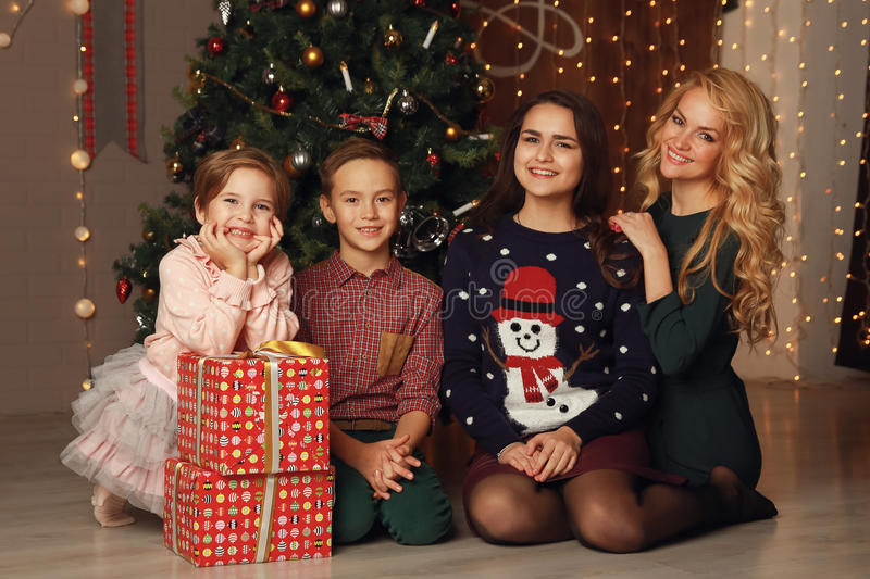 Happy family mother and children on Christmas at the Christmas tree with gifts stock photography