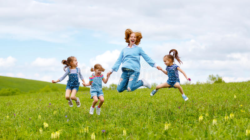 Happy family mother and children daughter girls laughing and jump on meadow in summer royalty free stock images