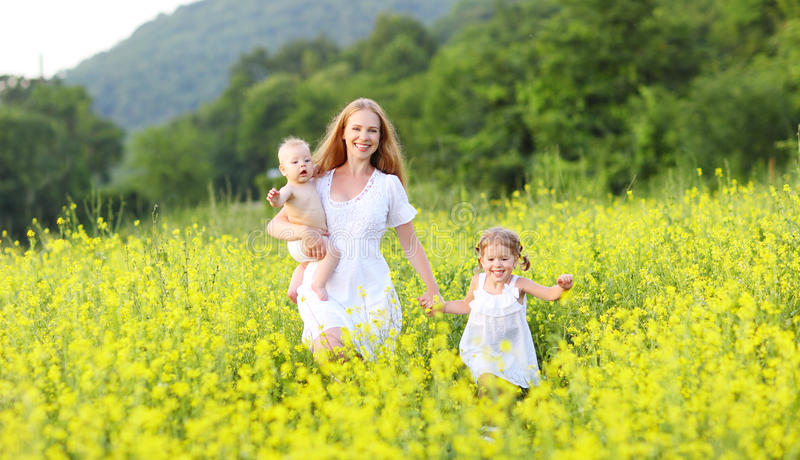 happy family, mother and children little daughter and baby running on meadow with yellow flowers stock photo