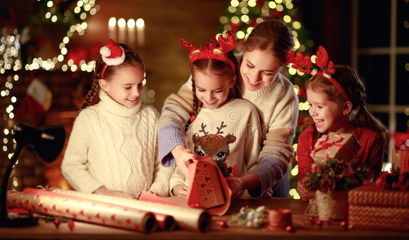 Happy family mother and children pack Christmas gifts stock photos