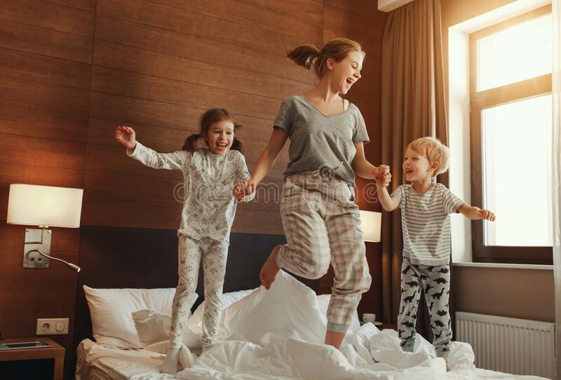 Happy family mother and children son and daughter jumping, laughing, playing in bed stock image