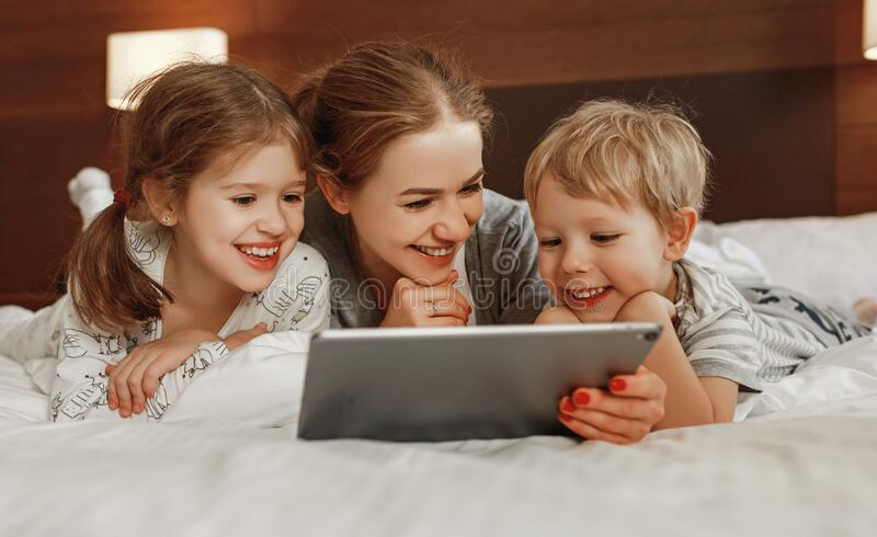 Happy family mother and children with tablet computer at home in bed in   evening stock images