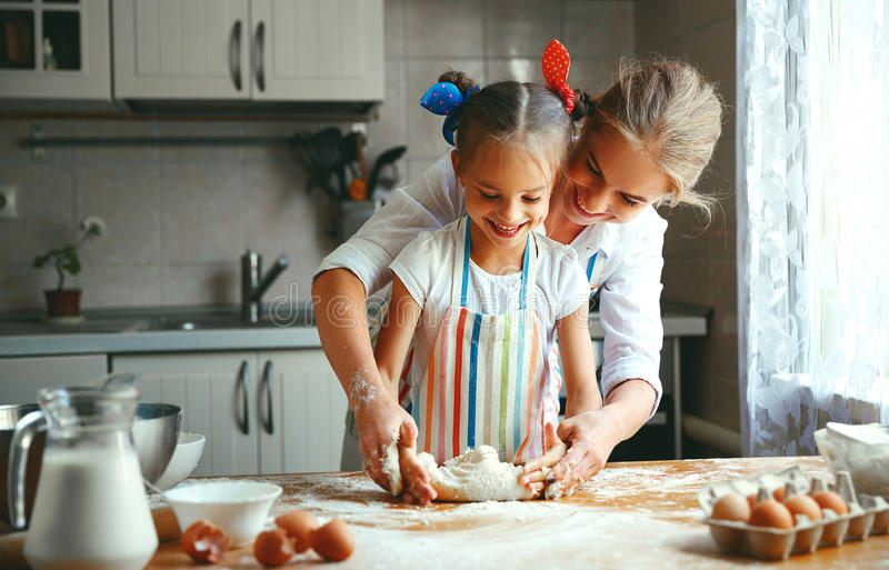 Happy family mother and daughter bake kneading dough in kitchen. Happy family mother and child daughter bake kneading dough in the kitchen royalty free stock photography