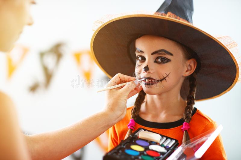 Happy family getting ready for halloween make make-up. Happy family mother and daughter getting ready for halloween make make-up royalty free stock image