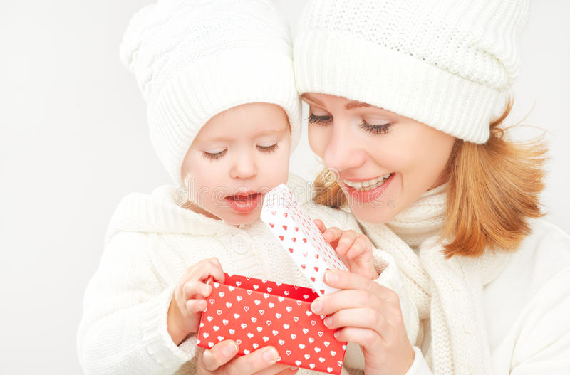 Happy family mother and daughter in hats with Christmas present in winter stock photography