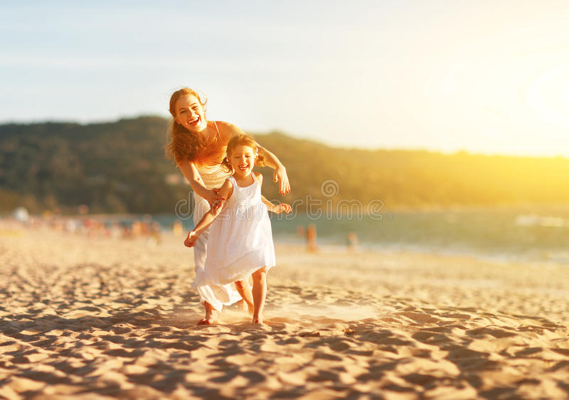 Happy family mother and daughter run, laugh and play at beach stock image