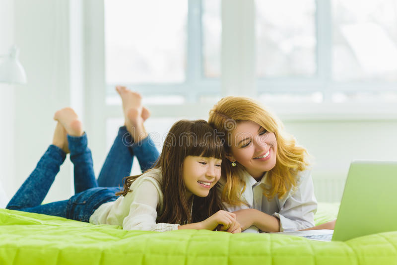 Happy family. Mother and daughter sitting on the bed with a laptop royalty free stock photography