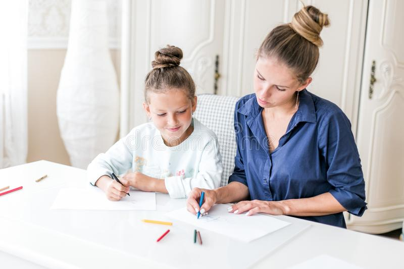 Happy family. Mother and daughter together paint and draw. Adult woman helps the child girl royalty free stock photos