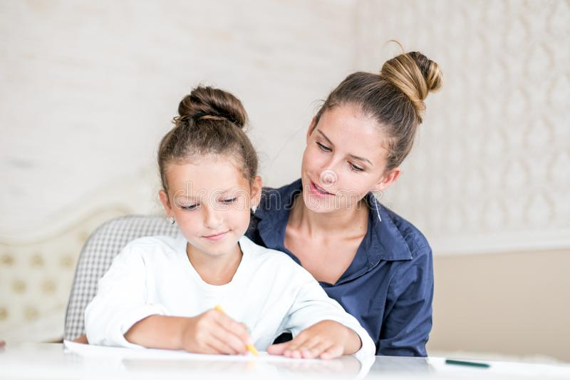 Happy family. Mother and daughter together paint and draw. Adult woman helps the child girl. Happy family. Mother and daughter together paint and draw. Adult royalty free stock photography