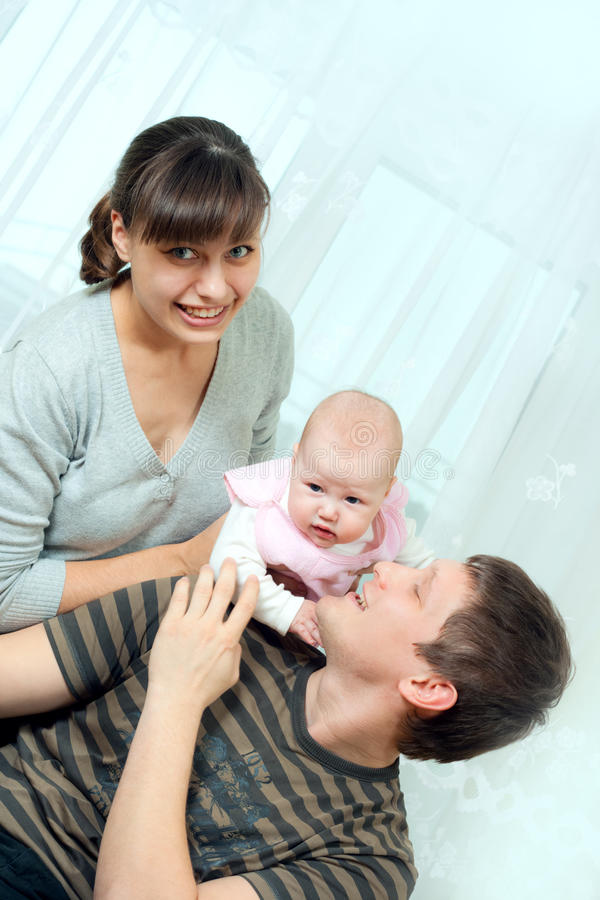 Happy family - mother, father and baby stock photos