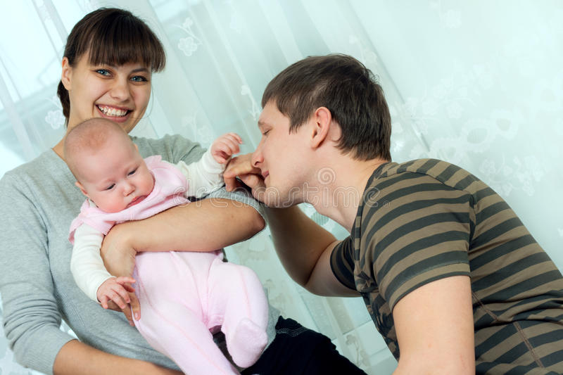 Happy family - mother, father and baby stock images