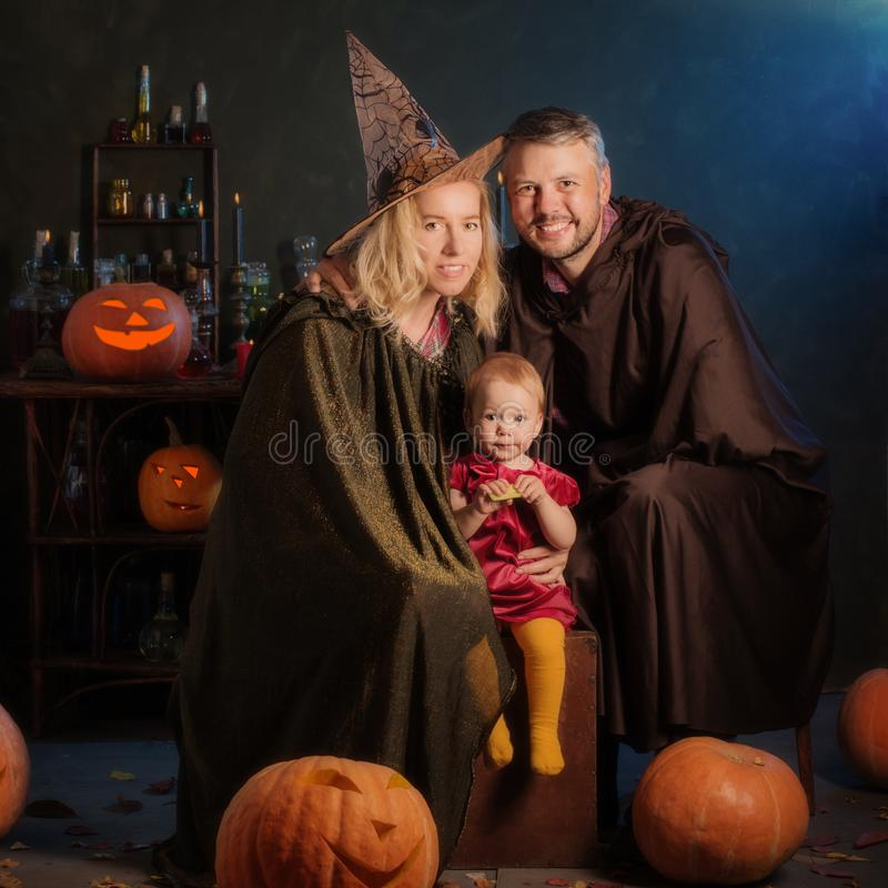 Happy family mother father and baby in costumes  on  celebration of Halloween stock photo