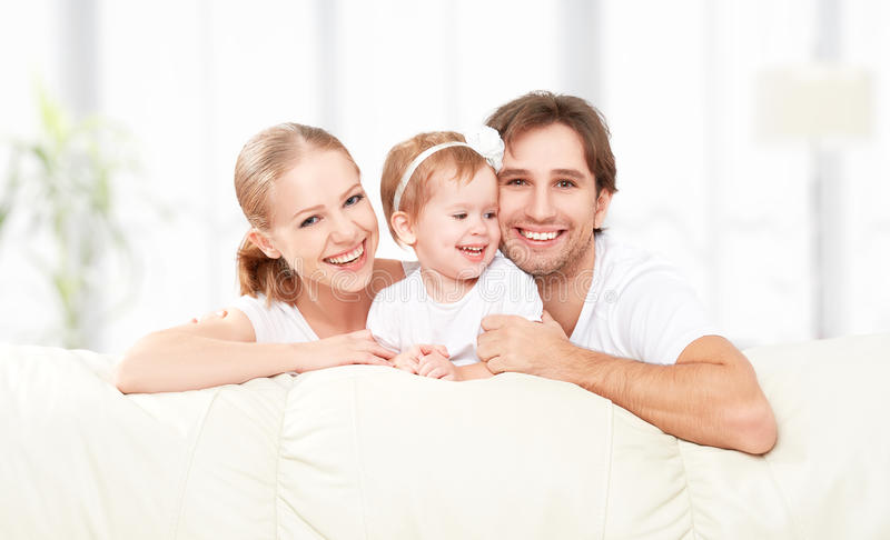 Happy family mother, father, child baby daughter at home on sofa playing and laughing stock photo