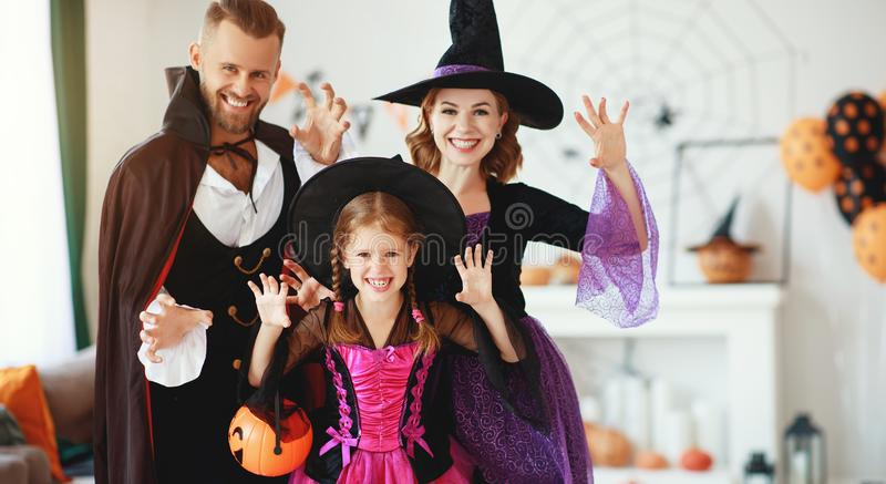 Happy family mother father and child daughter in costumes   on  Halloween. Happy family mother father and child daughter in costumes   on a celebration of royalty free stock photography