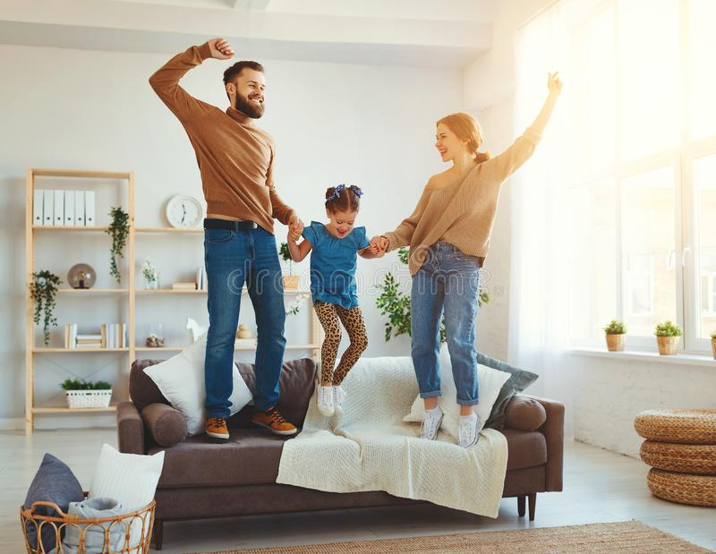 Happy family mother father and child daughter dancing. At home stock photography