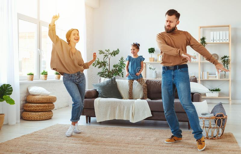 Happy family mother father and child daughter dancing at home. A happy family mother father and child daughter dancing at home royalty free stock images