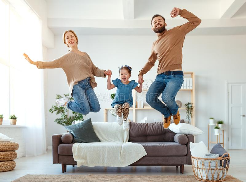 Happy family mother father and child daughter dancing at home. A happy family mother father and child daughter dancing at home stock image