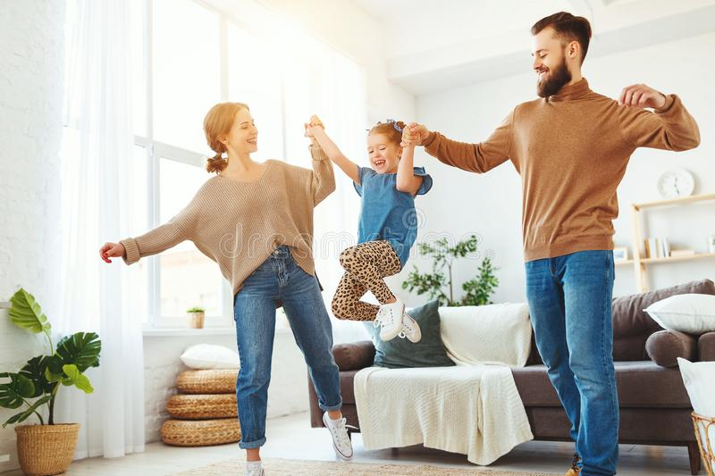 Happy family mother father and child daughter dancing at home. A happy family mother father and child daughter dancing at home stock photos