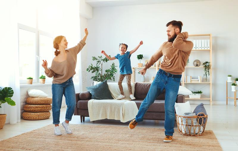 Happy family mother father and child daughter dancing at home. A happy family mother father and child daughter dancing at home royalty free stock photo