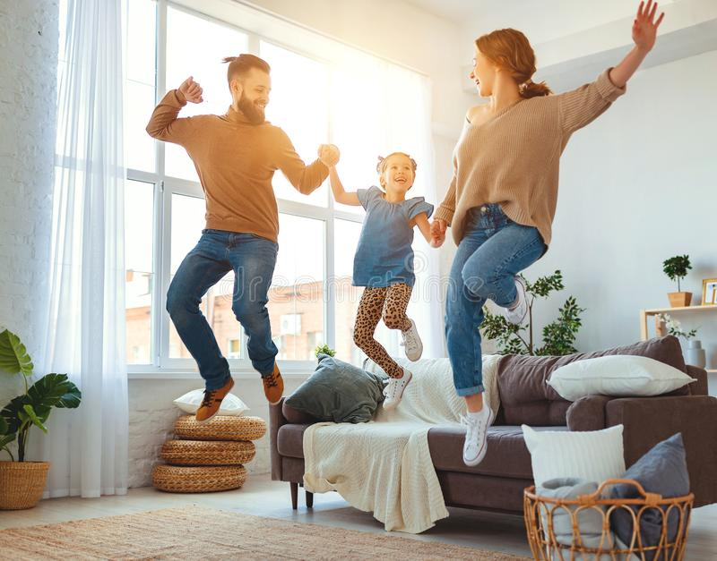 Happy family mother father and child daughter dancing at home. A happy family mother father and child daughter dancing at home stock images
