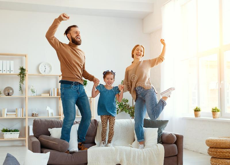 Happy family mother father and child daughter dancing at home stock photo
