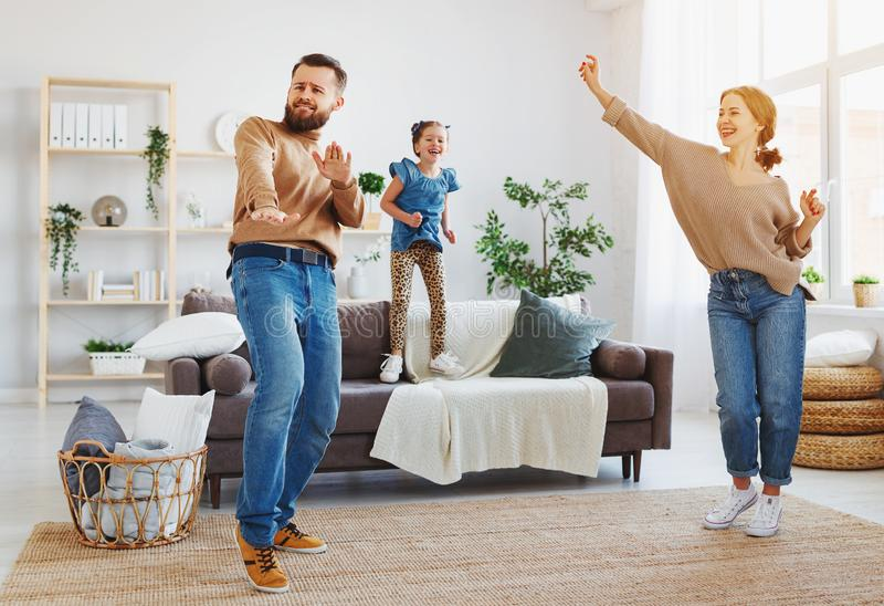 Happy family mother father and child daughter dancing at home. A happy family mother father and child daughter dancing at home royalty free stock photography
