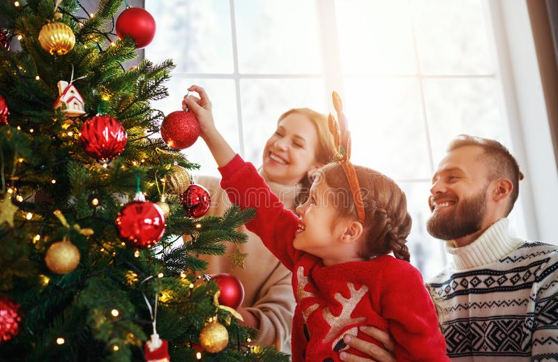 Happy family mother, father and child daughter decorate Christmas tree royalty free stock photo