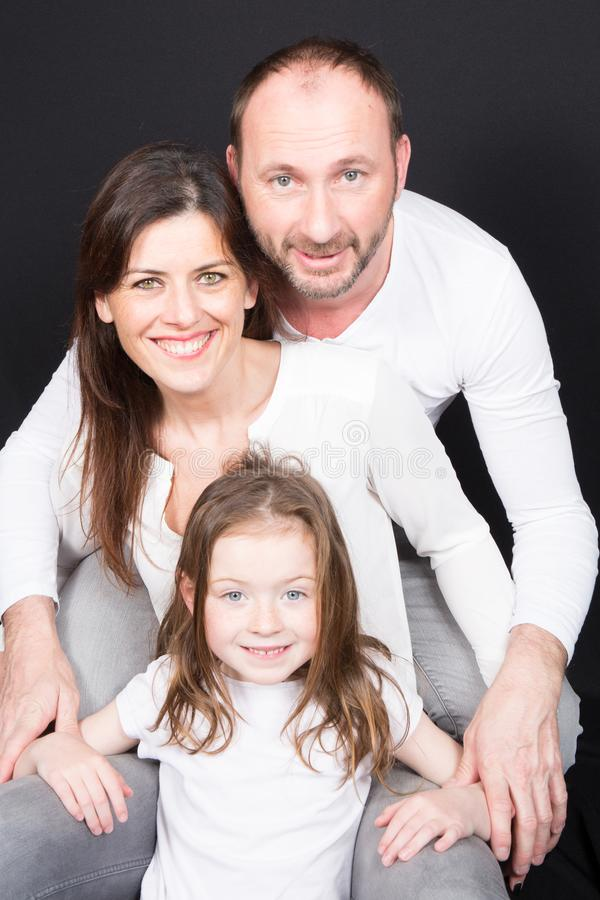 Happy family mother, father, child daughter at home front black background wall stock image