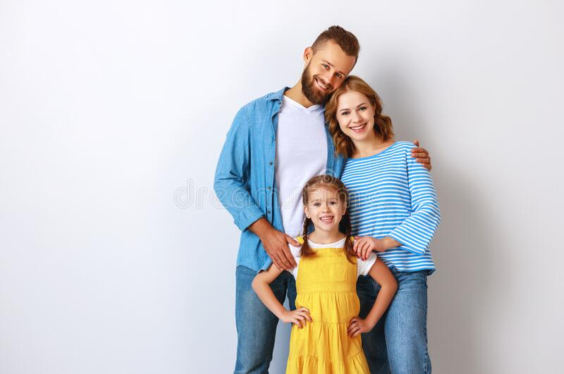 Happy family mother father and child  near an empty brick wall royalty free stock photography