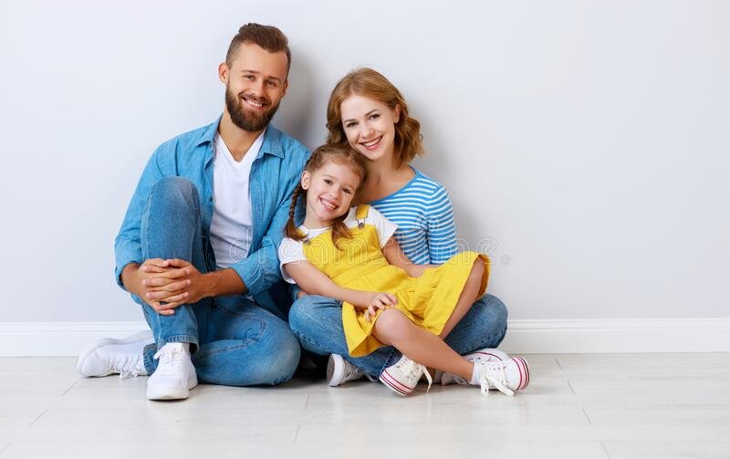 Happy family mother father and child  near an empty brick wall stock image