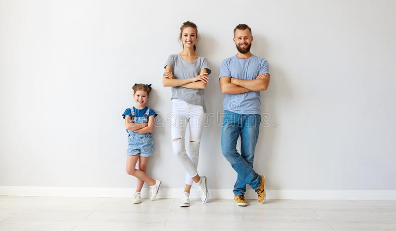 Happy family mother father and child  near an empty wall. Happy family mother father and child daughter near an empty wall stock images