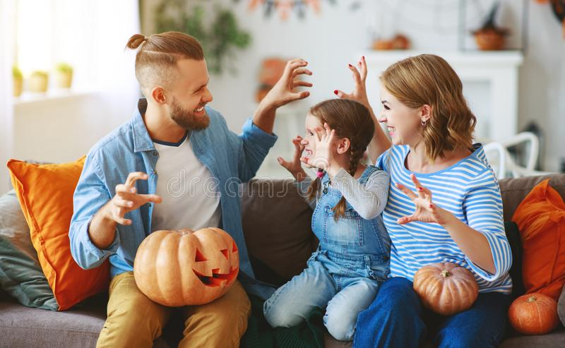 Happy  family mother father and child daughter prepare for Halloween decorate  home with pumpkins,  laughing and  play stock photo