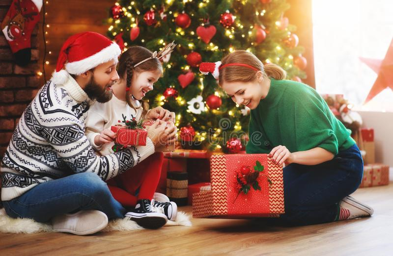 Happy family mother, father and child  with gifts near   Christmas tree at home stock images