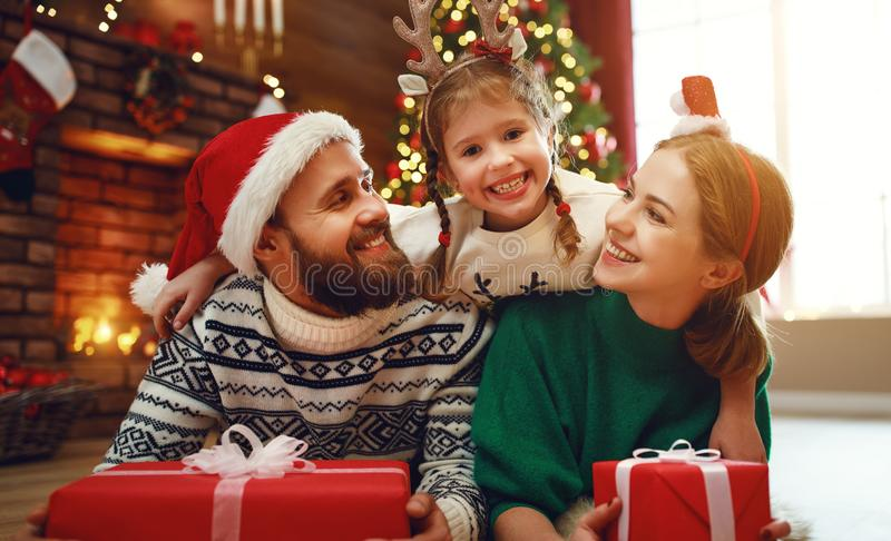 Happy family mother, father and child  with gifts near   Christmas tree at home stock photography