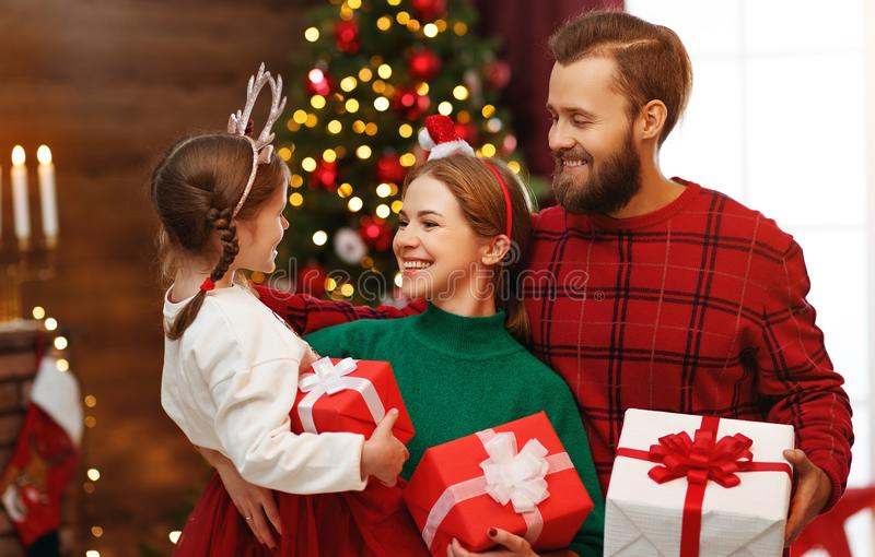 Happy family mother, father and child  with gifts near   Christmas tree at home stock photo