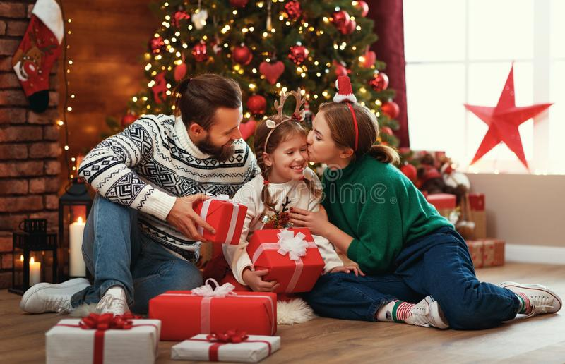 Happy family mother, father and child  with gifts near   Christmas tree at home royalty free stock image