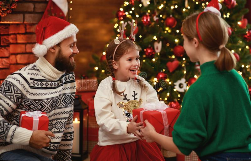 Happy family mother, father and child  with gifts near   Christmas tree at home royalty free stock photography