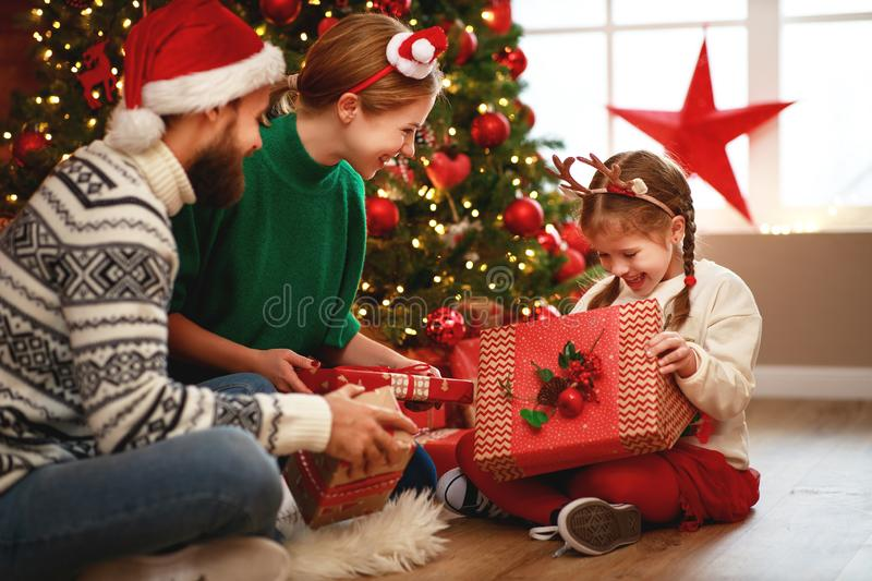 Happy family mother, father and child  with gifts near   Christmas tree at home stock photos